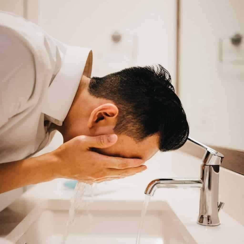Person washing their face in the sink.