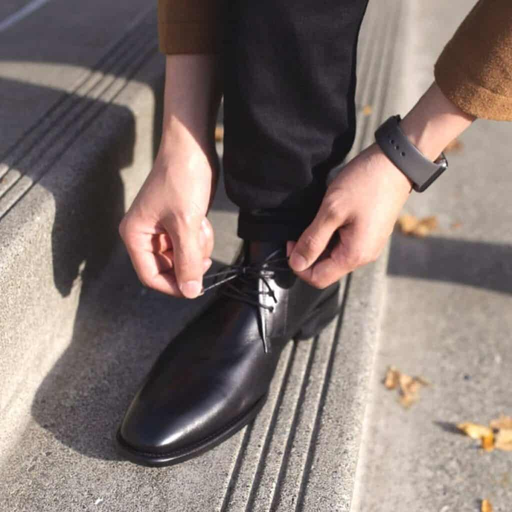 Close-up of a person tying the laces on their chukka boot.