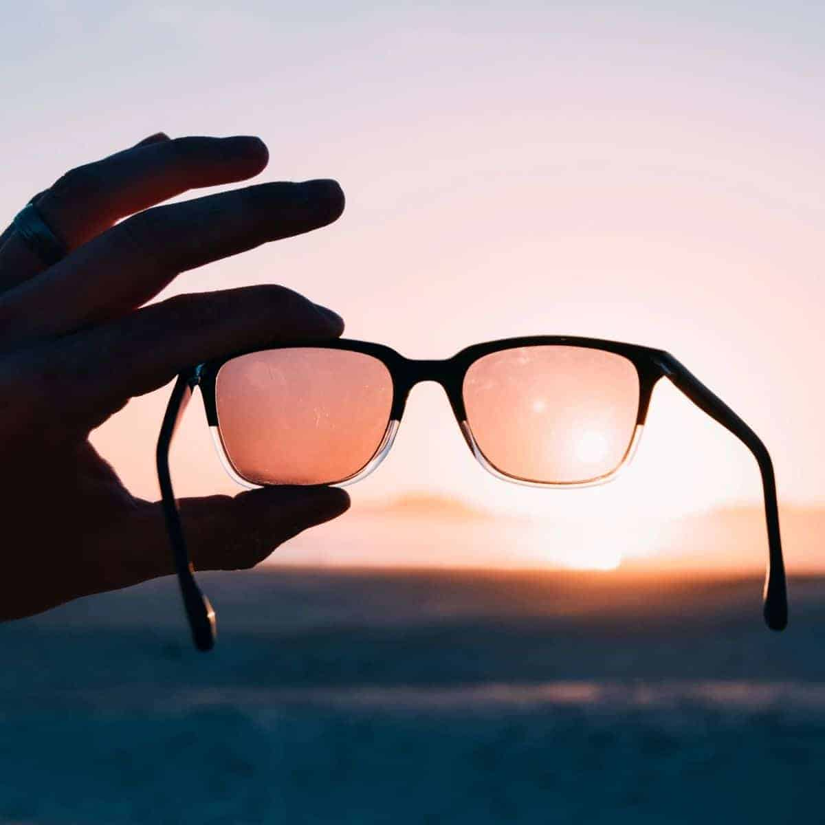 Close-up of a persons hand holding sunglasses up to a sunset.