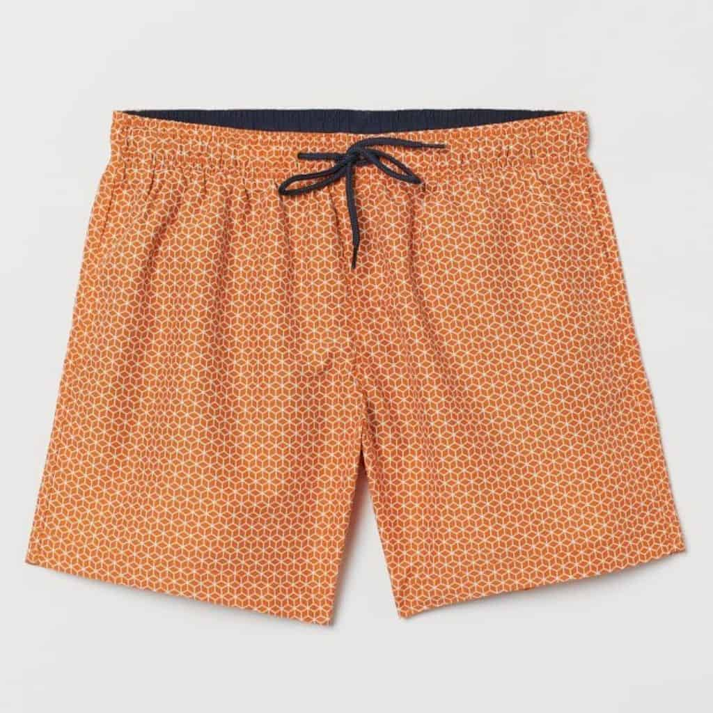 Orange swim trunks with a geometric print.