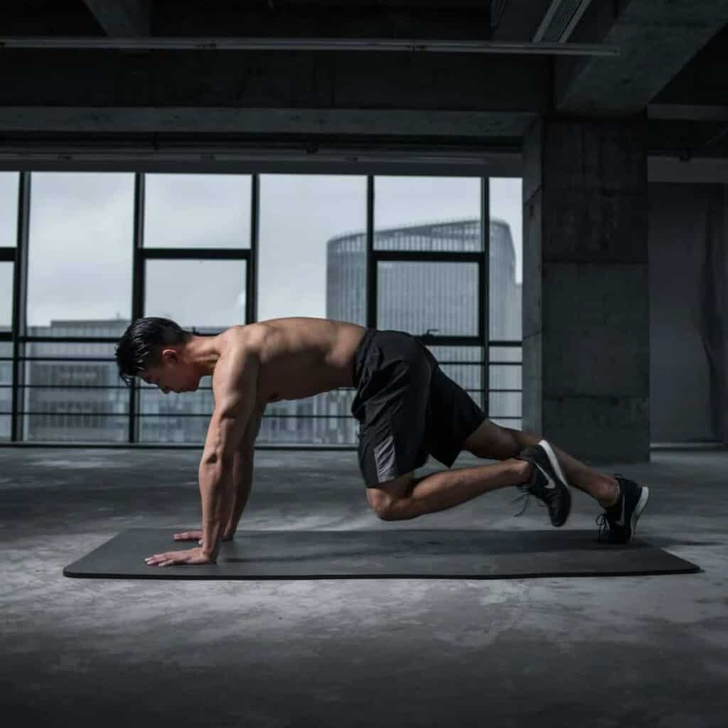 Person doing the mountain climbers exercise on a yoga mat.