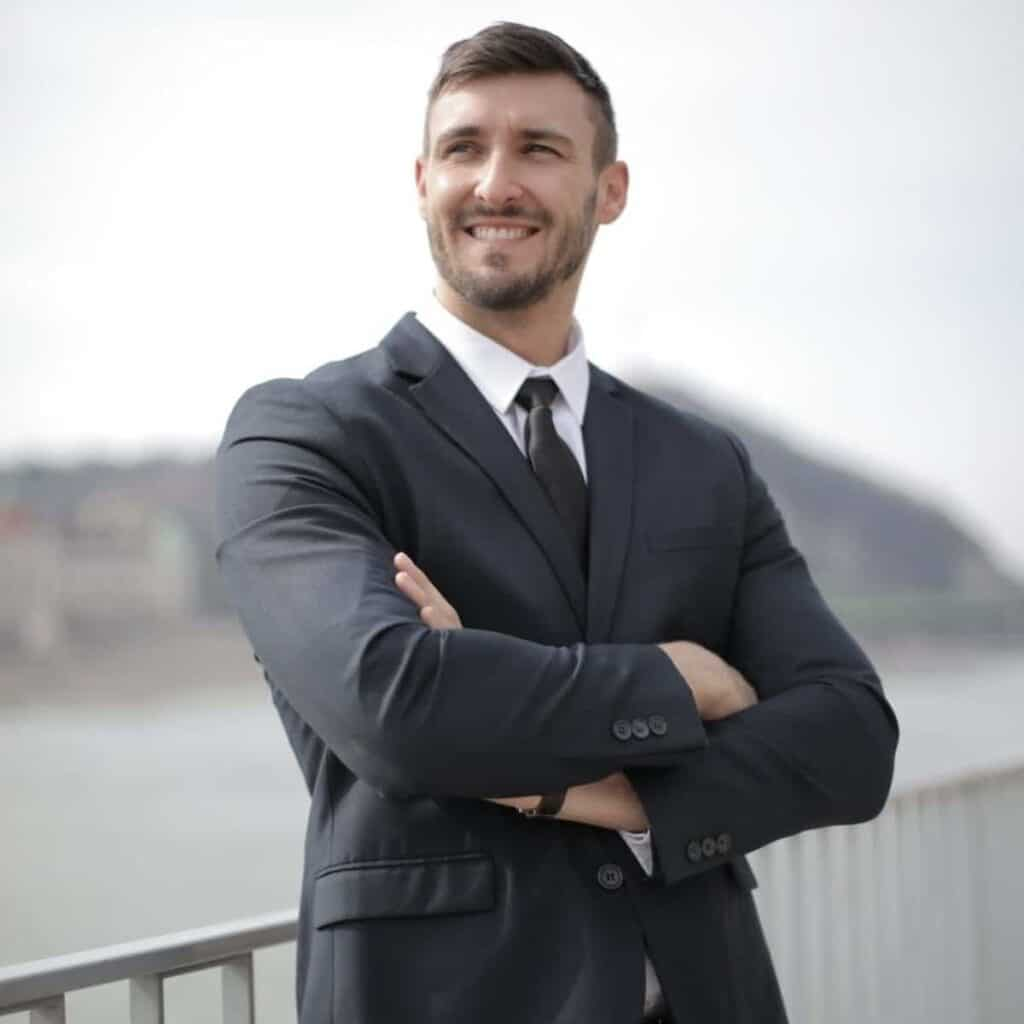 Person wearing a suit and smiling while leaning against a railing.