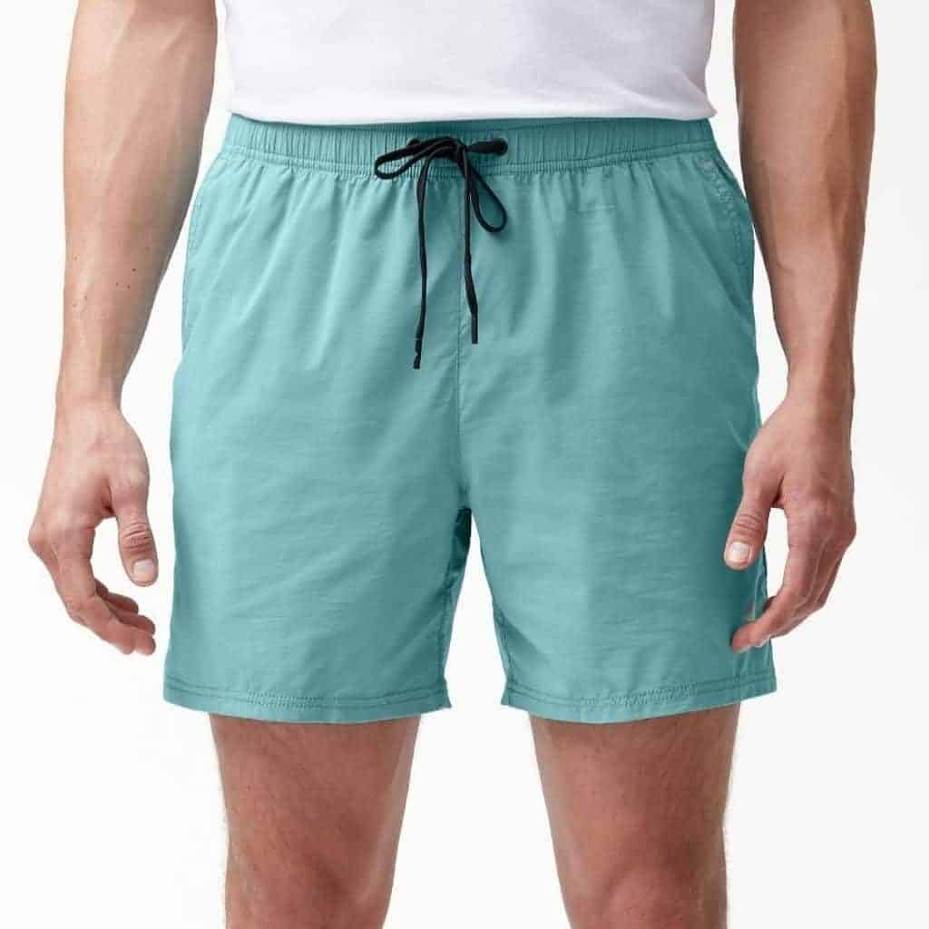 Close-up of a person wearing teal swim trunks and a white shirt.