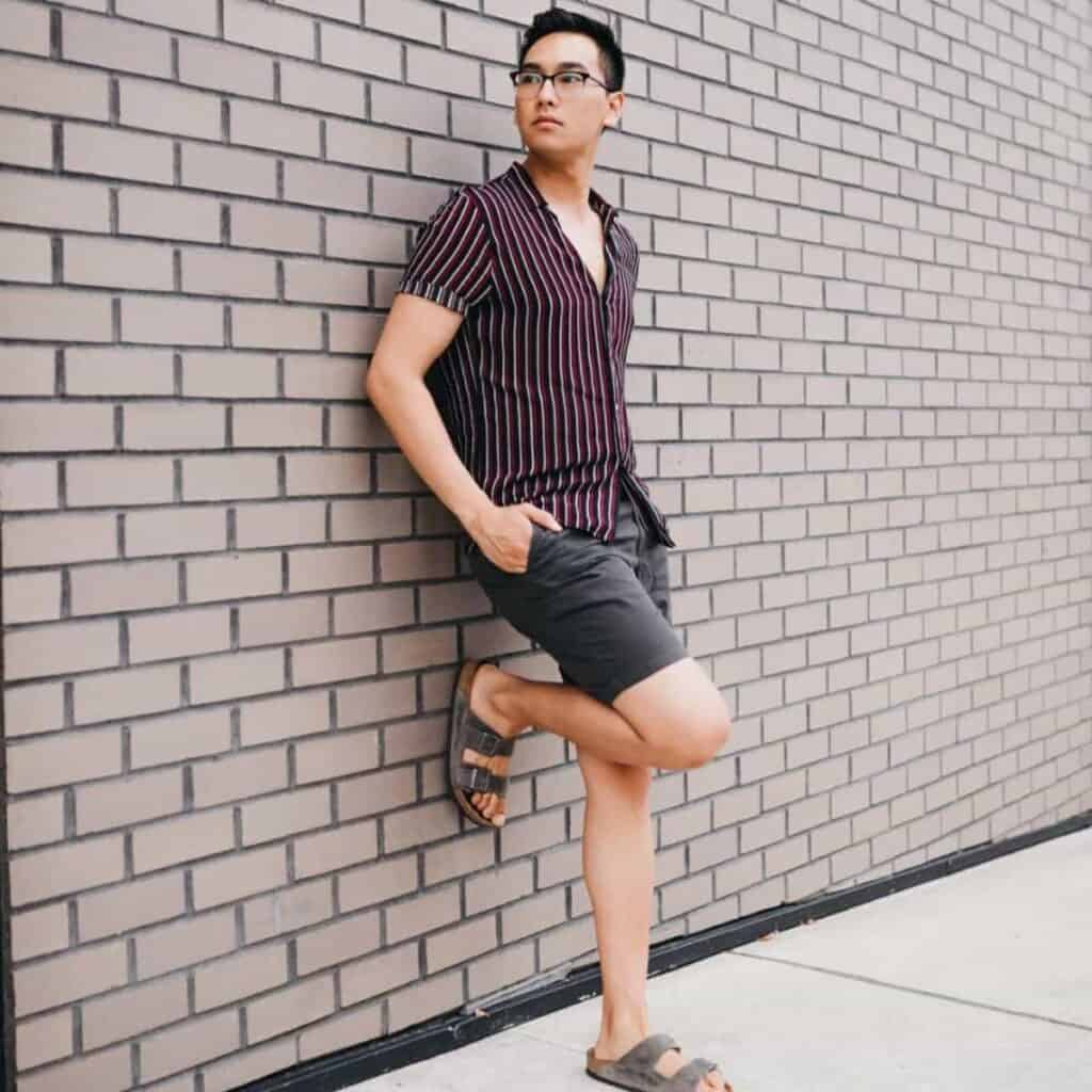 Person wearing shorts and leaning against a brick wall.