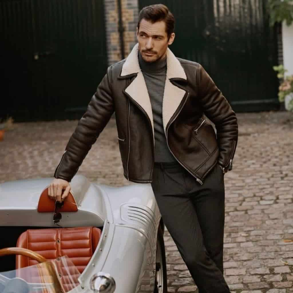 David Gandy wearing a leather jacket and leaning on a car.