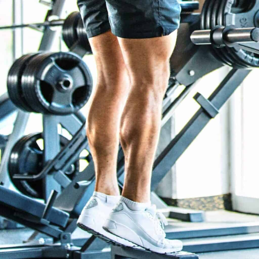 Close-up of a person doing calf raises in a gym.