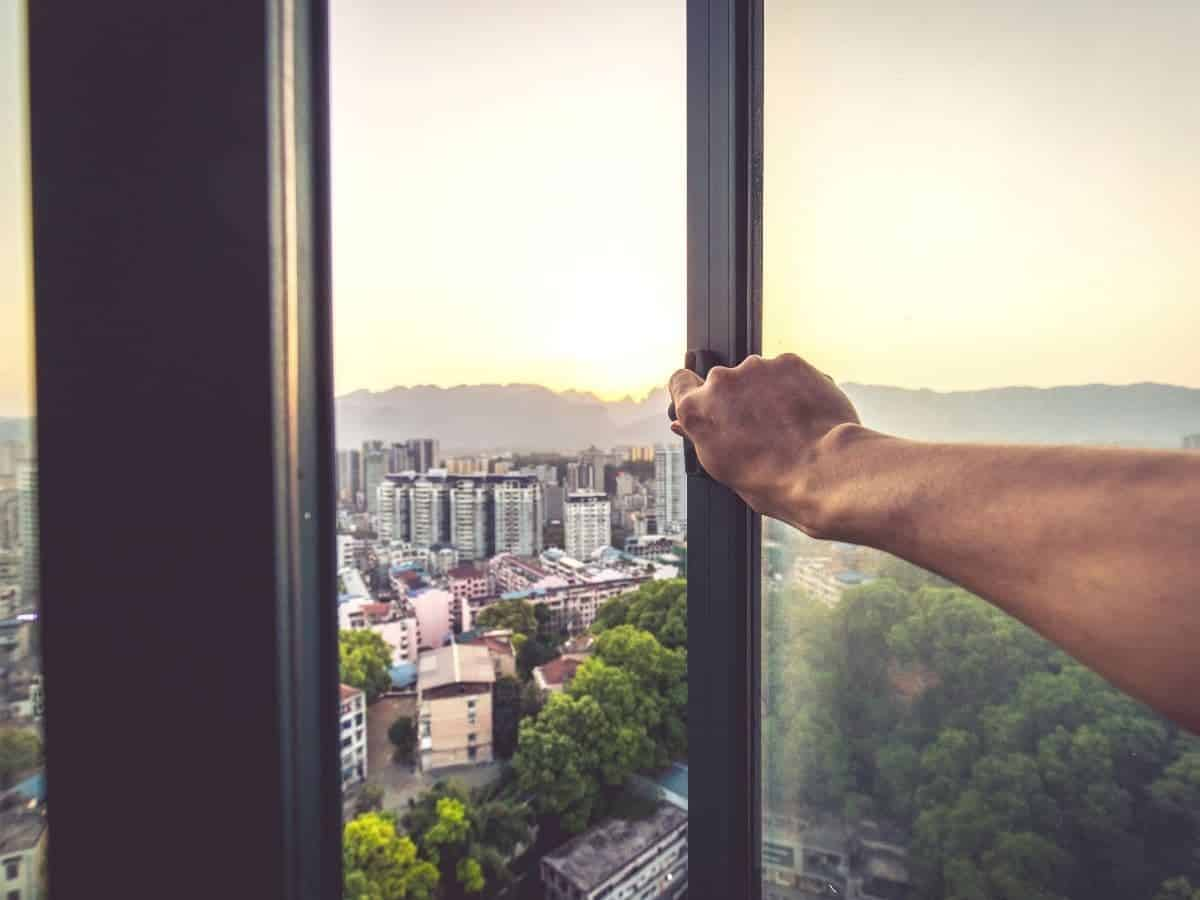Arm opening a window with a view of the city.