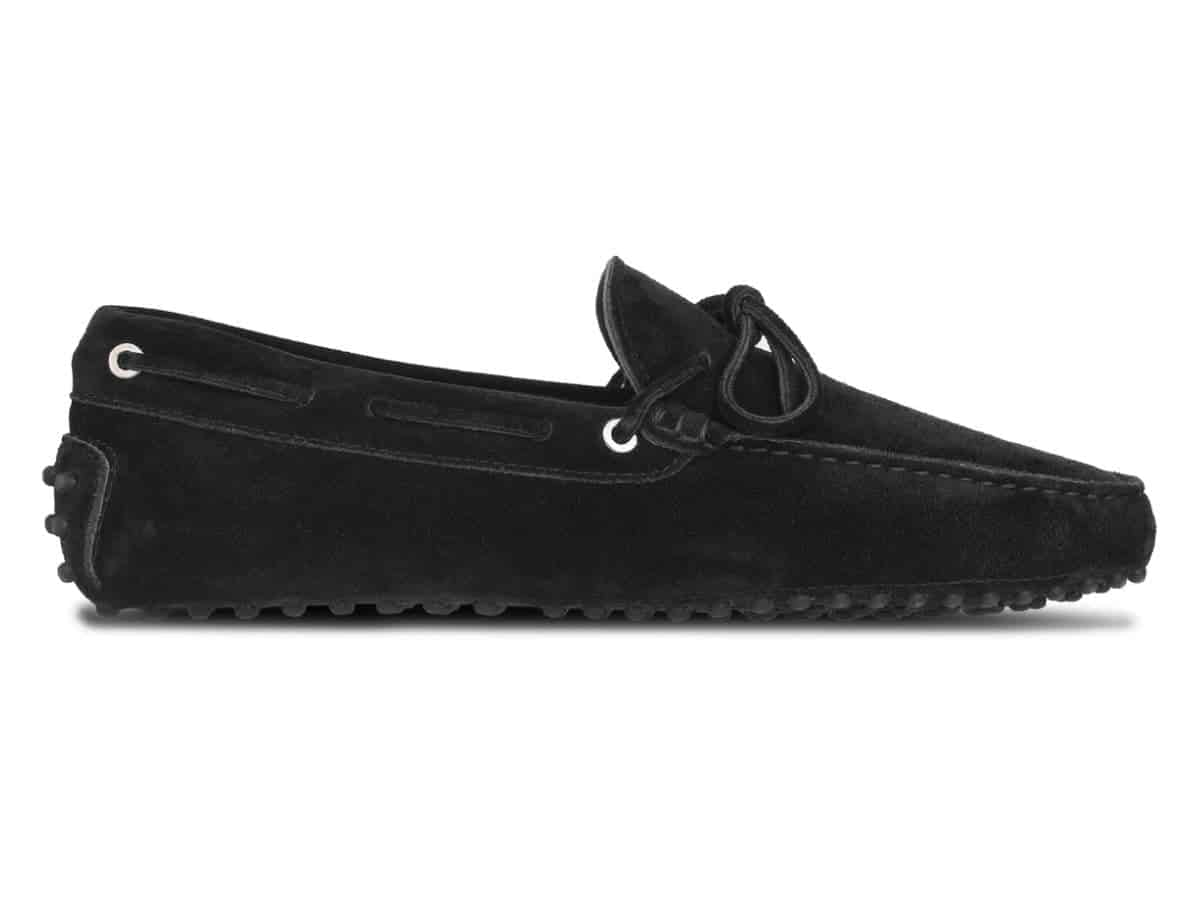 Side of a black suede driving shoe.