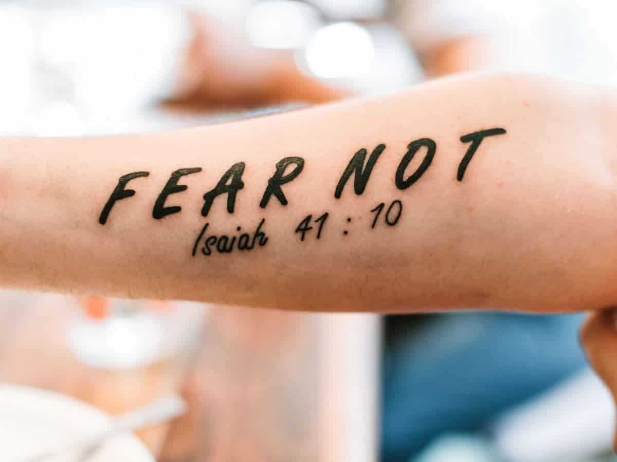 Bible verse tattoo on a person's arm.