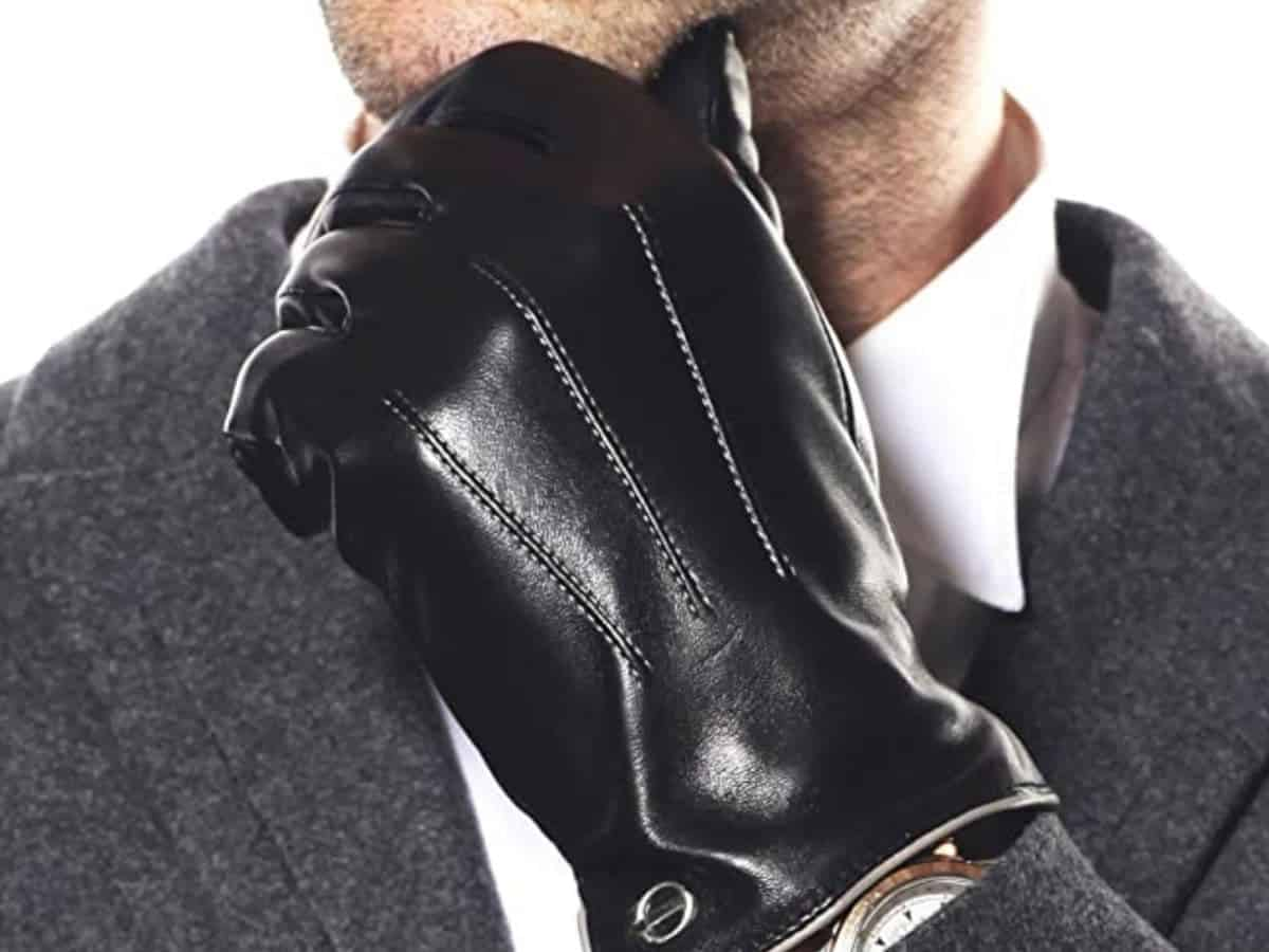 Close-up of black leather driving gloves on a person's hand.