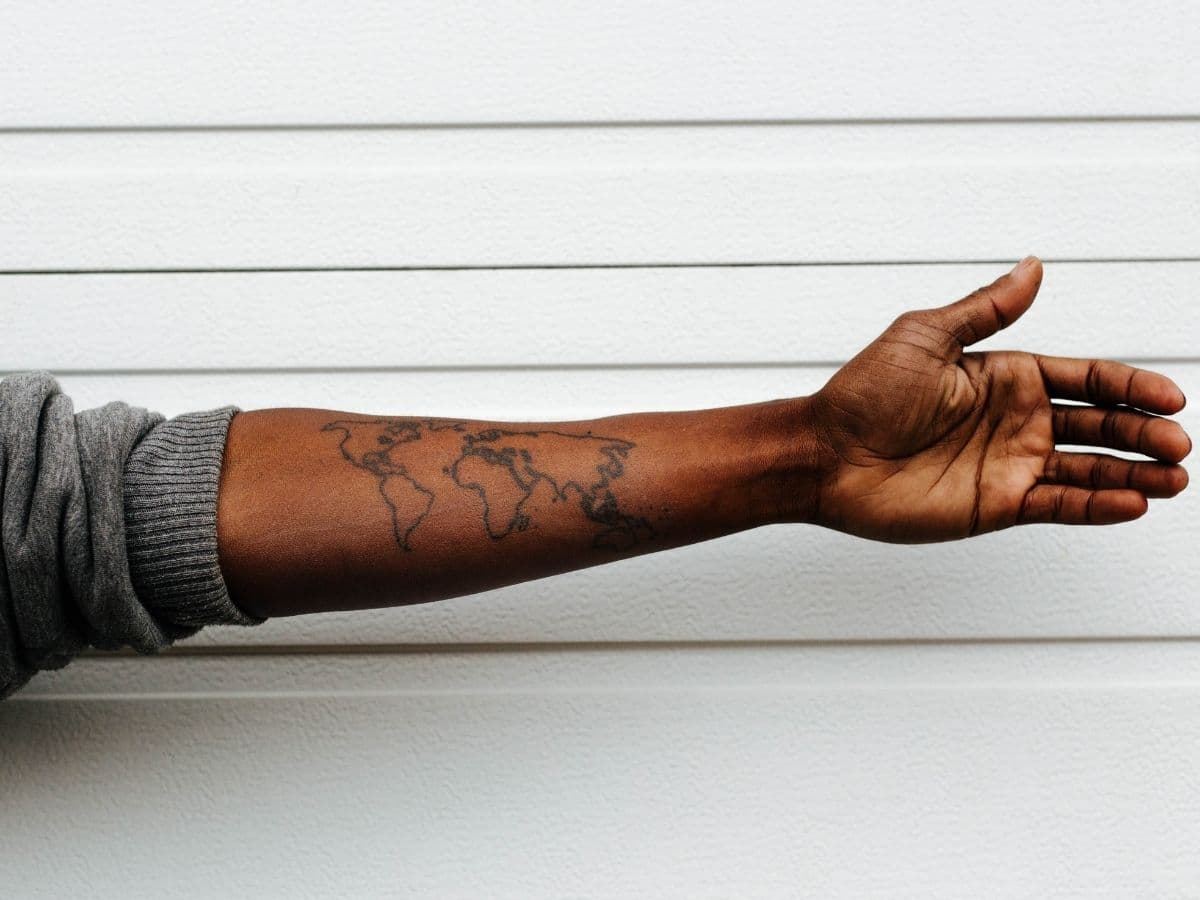 Tattoo of an outline of the continents on a person's arm.