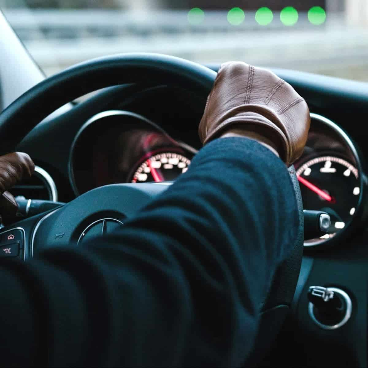 Person wearing leather driving gloves and holding a steering wheel.