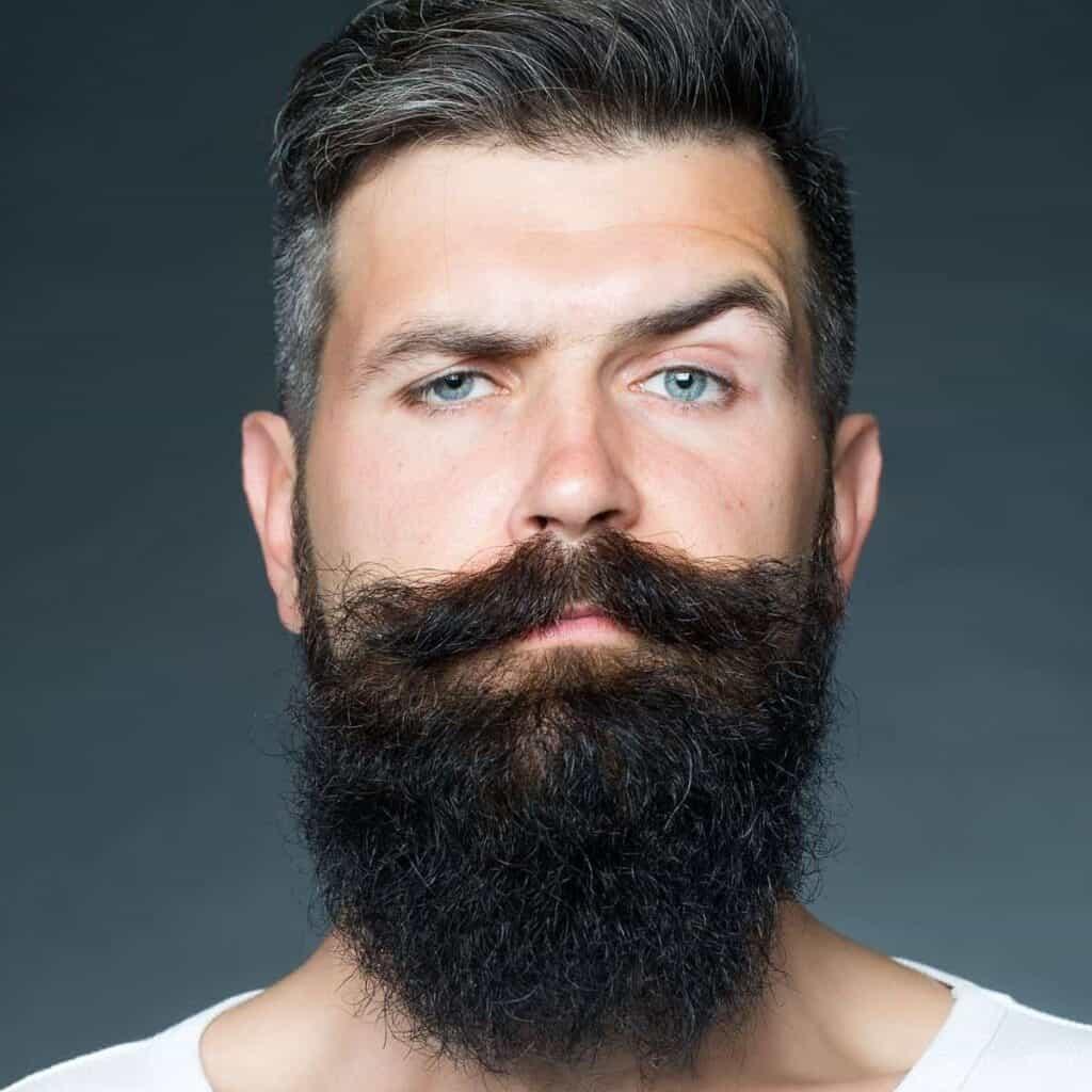 Person with a beard raising their eyebrow.