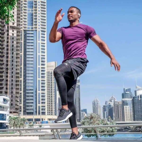 Person exercising outdoors with high-rise buildings in the background.