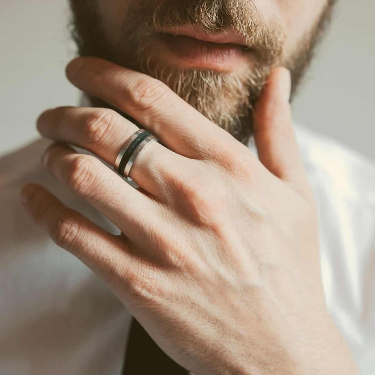 Close-up of a ring on a person's hand while they touch their beard.