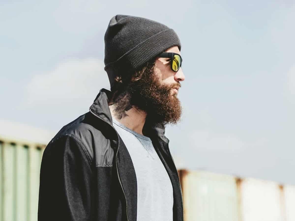 Person wearing a beanie and sunglasses and looking to the side.