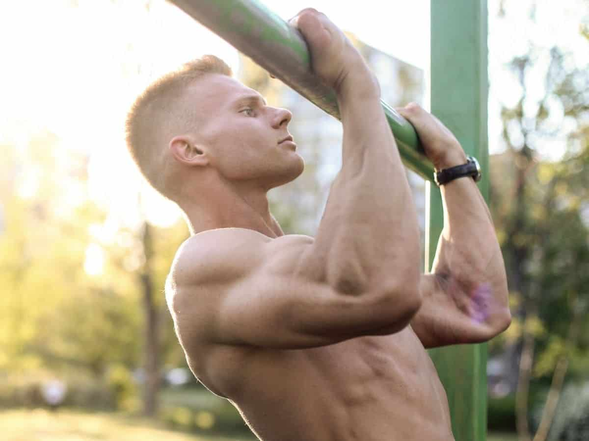 Person doing chin-ups outside.