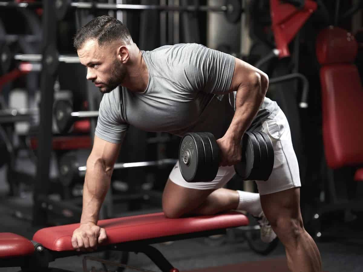 Person on a bench doing a dumbbell row.