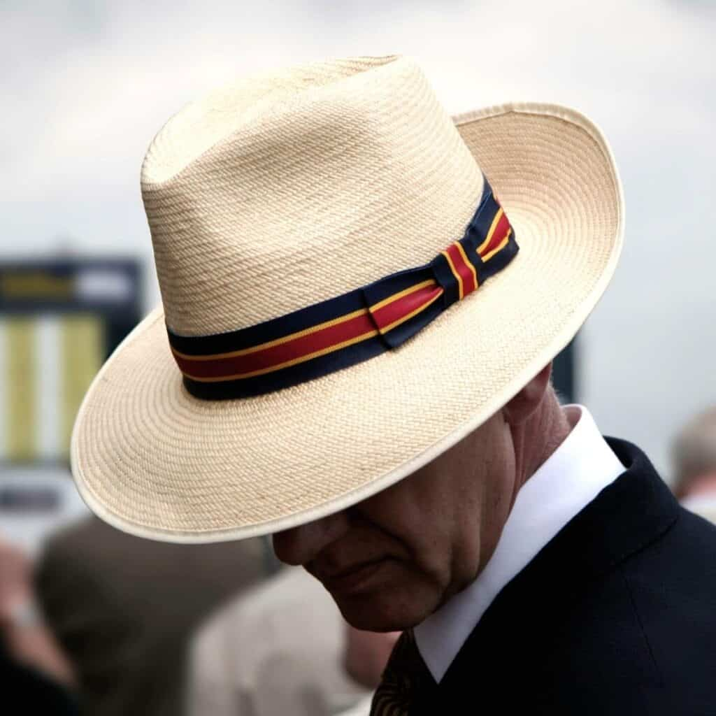 Person wearing a hat and looking down.