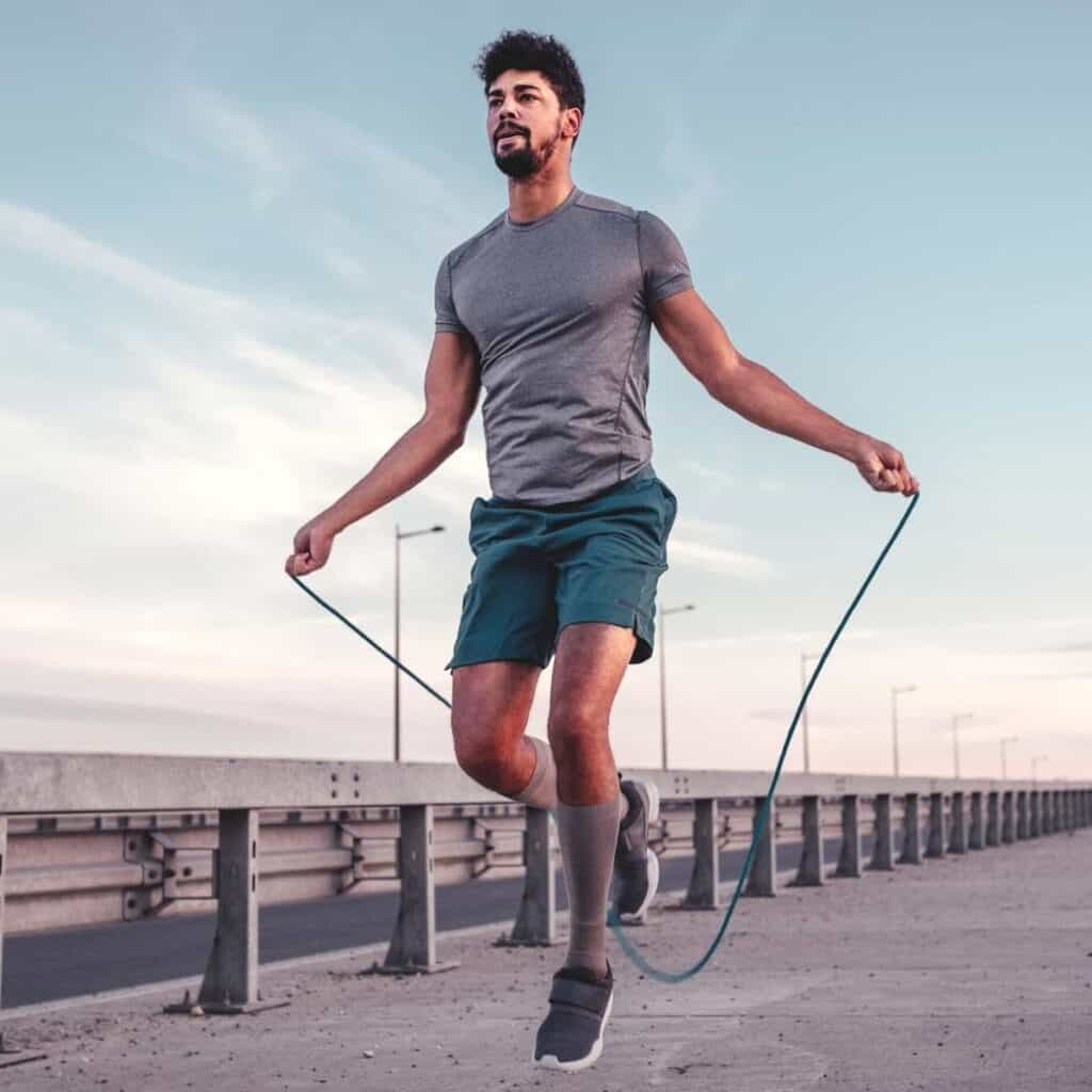 Person jumping rope on a sidewalk.
