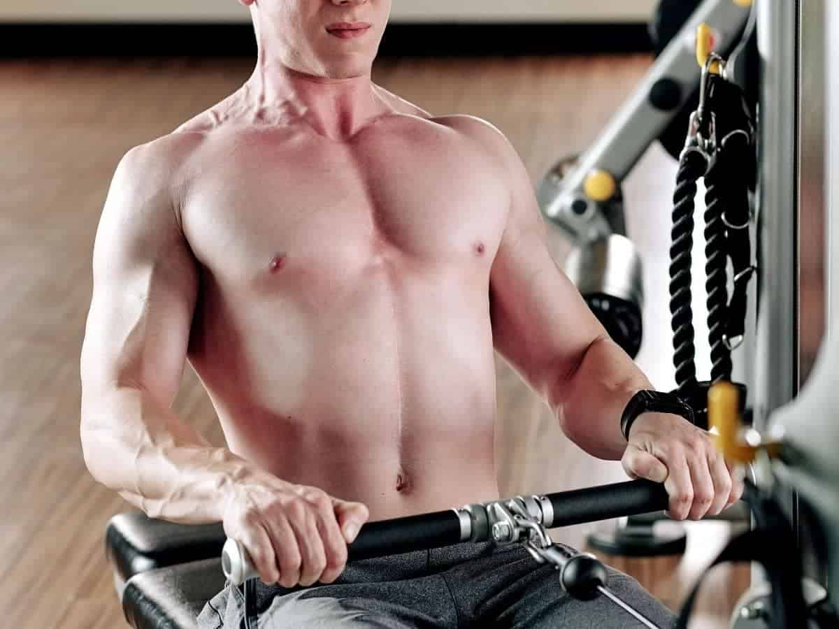 Shirtless person doing a cable row.