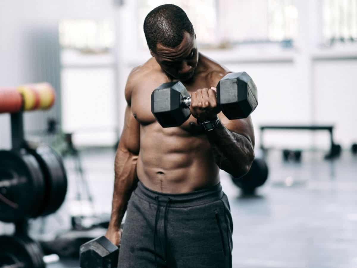 Shirtless person doing dumbbell curls.