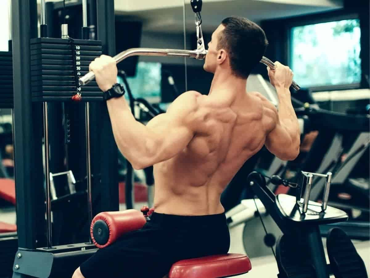 Shirtless person doing a lat pulldown.