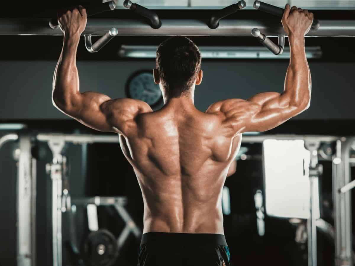 Shirtless person doing pull-ups.