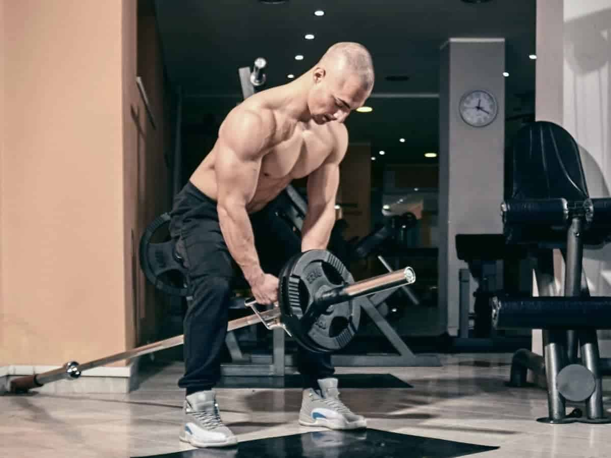 Shirtless person doing a T-bar row.