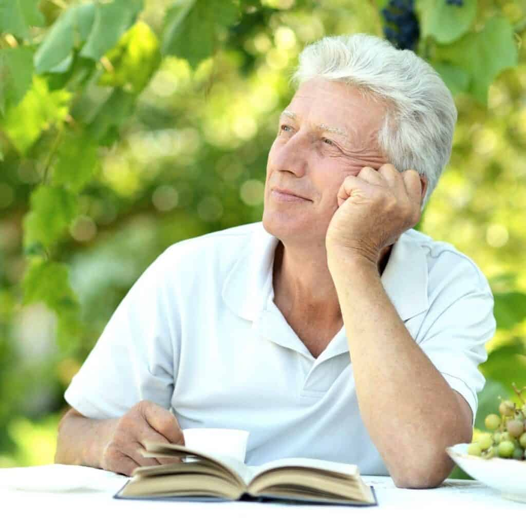 Man sitting at a table with a book outdoors and looking to the side.