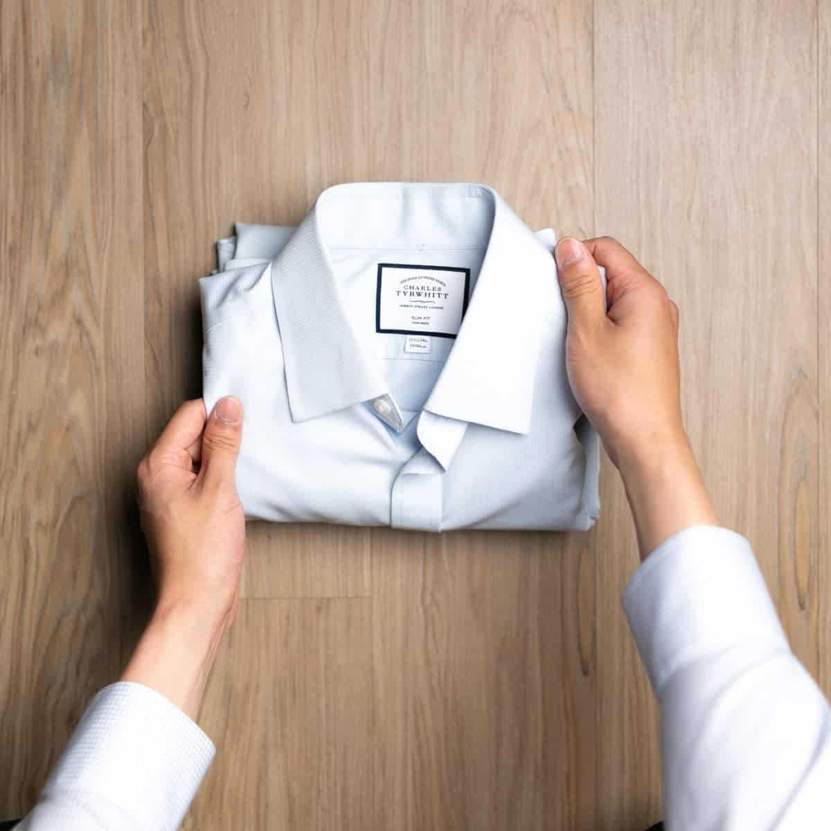 Person's hands folding a dress shirt.
